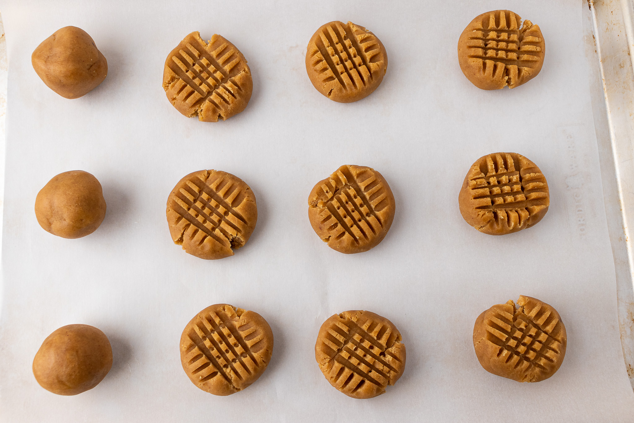 Peanut butter cookies on a cookie sheet before baking
