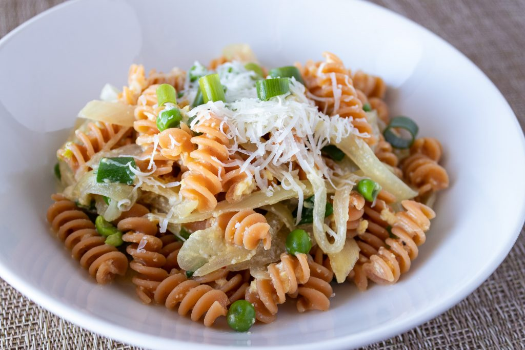 Lentil pasta with green peas, onions, eggs, and cheese